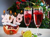Dos vidrios con el champán y las velas rojos 2015 Foto de archivo libre de regalías