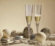 Dos vidrios con el champange, las cajas de regalo y las decoraciones de la Navidad Foto de archivo libre de regalías
