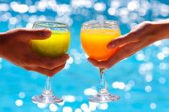 Dos vidrios con el jugo contra el agua azul Foto de archivo libre de regalías