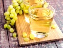 Dos vidrios con el jugo de uva en la tabla de madera Foto de archivo