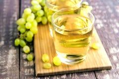 Dos vidrios con el jugo de uva en la tabla de madera Imagen de archivo