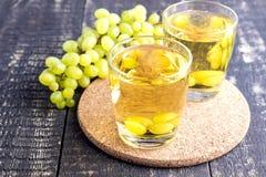Dos vidrios con el jugo de uva en la tabla de madera Fotos de archivo