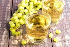 Dos vidrios con el jugo de uva en la tabla de madera Fotos de archivo libres de regalías