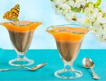 Dos vidrios con el postre y la mariposa, primer Imagen de archivo libre de regalías