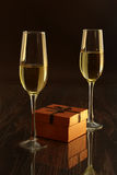 Dos vidrios con el vino blanco y la caja de regalo en la tabla del espejo Composición de las celebridades Foco selectivo Imagen de archivo libre de regalías