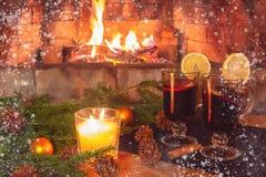 Dos vidrios con el vino reflexionado sobre, una vela, ramas del abeto con las decoraciones en una tabla de madera contra la persp imagen de archivo
