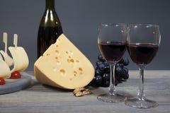 Dos vidrios con el vino rojo en una tabla de madera El queso y el manojo de uvas armonioso complementan la composición Foto de archivo libre de regalías