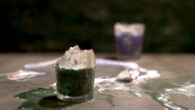 Dos vidrios con las bebidas alcohólicas multicoloras chocan en la tabla y la rotura en fragmentos Cámara lenta metrajes