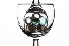 Dos vidrios con las cuentas de cristal en un fondo blanco Fotografía de archivo