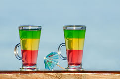Dos vidrios con los cócteles coloridos en el fondo del mar Fotografía de archivo