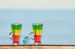 Dos vidrios con los cócteles coloridos en el fondo del mar Imagen de archivo libre de regalías