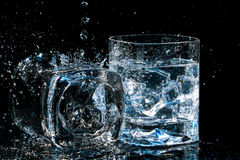Dos vidrios de alta calidad del whisky, uno mienten en lado con agua salpican y otro con los cubos de hielo Fotografía de archivo