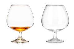 Dos vidrios de brandy (vacie y con alcohol) aislados en los vagos blancos Imágenes de archivo libres de regalías