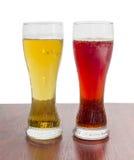 Dos vidrios de cerveza con la cerveza de cerveza dorada y la cerveza oscura Fotografía de archivo