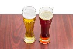 Dos vidrios de cerveza con la cerveza de cerveza dorada y la cerveza oscura Fotografía de archivo libre de regalías