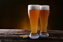 Dos vidrios de cerveza en fondo de madera marrón Imágenes de archivo libres de regalías