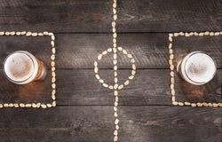 Dos vidrios de cerveza en marcas miniatura del campo de fútbol del cacahuete Fotografía de archivo libre de regalías