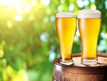 Dos vidrios de cerveza en un barril de madera. Foto de archivo libre de regalías