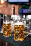Dos vidrios de cerveza en una tabla de la barra Golpecito de la cerveza en fondo Foto de archivo