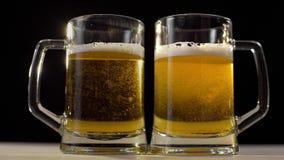 Dos vidrios de cerveza se vierten con la cerveza ligera de oro espumosa en el fondo negro, cerveza con el amigo, beben para dos p almacen de metraje de vídeo