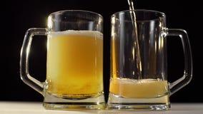 Dos vidrios de cerveza se vierten con la cerveza ligera de oro espumosa en el fondo negro, cerveza con el amigo, beben para dos p metrajes