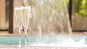 Dos vidrios de champán cerca del Jacuzzi al aire libre Imágenes de archivo libres de regalías
