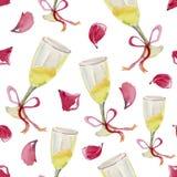 Dos vidrios de champán, de cinta rosada y de pétalos color de rosa que caen Imagen de archivo