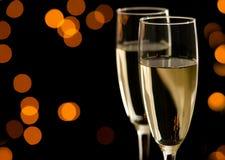 Dos vidrios de champán con el bokeh de oro Imagenes de archivo