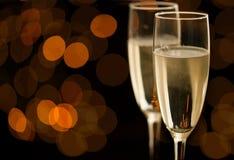 Dos vidrios de champán con el bokeh de oro Fotografía de archivo