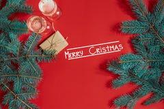 Dos vidrios de champán con la rama de árbol de navidad y el pequeño regalo en un fondo rojo Imagenes de archivo