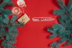 Dos vidrios de champán con la rama de árbol de navidad y el pequeño regalo en un fondo rojo Imágenes de archivo libres de regalías