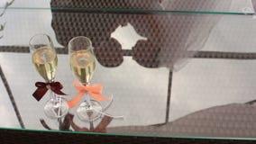 Dos vidrios de champán con las cintas coloridas en la tabla Reflexión de los pares de la boda sobre el vidrio almacen de video