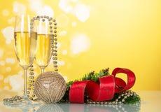 Dos vidrios de champán con las decoraciones de la Navidad en un amarillo Fotos de archivo