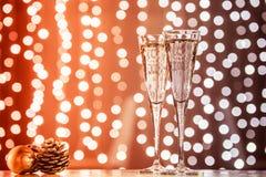 Dos vidrios de champán con los juguetes de la Navidad Bok festivo de las luces Fotos de archivo