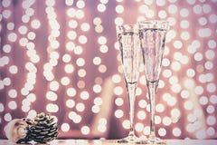 Dos vidrios de champán con los juguetes de la Navidad Bok festivo de las luces Fotos de archivo libres de regalías