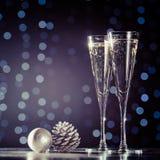 Dos vidrios de champán con los juguetes de la Navidad Bok festivo de las luces Foto de archivo