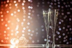 Dos vidrios de champán con los juguetes de la Navidad Bok festivo de las luces Imagen de archivo libre de regalías