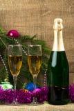 Dos vidrios de champán en el fondo de la Navidad, y una botella de vino fotografía de archivo libre de regalías