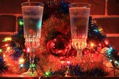 Dos vidrios de champán en un fondo de las decoraciones de la Navidad Fotografía de archivo libre de regalías