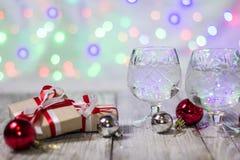 Dos vidrios de champán de la Navidad con las cajas de regalo y las decoraciones de las bolas contra fondo ligero del bokeh Imágenes de archivo libres de regalías