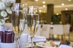 Dos vidrios de champán que esperan para ser servido por las huéspedes Fotos de archivo