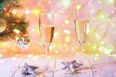 Dos vidrios de champán se colocan en una tabla de madera blanca en el fondo de un árbol y de guirnaldas del Año Nuevo Bokeh de la Foto de archivo libre de regalías