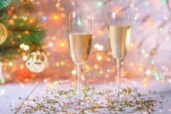 Dos vidrios de champán se colocan en una tabla de madera blanca en el fondo de un árbol y de guirnaldas del Año Nuevo Bokeh de la Fotos de archivo libres de regalías