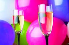Dos vidrios de champán y de globos en partido Imagenes de archivo