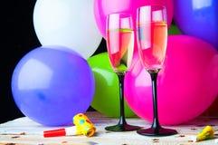 Dos vidrios de champán y de globos en partido Foto de archivo