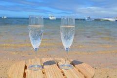 Dos vidrios de Champagne On la playa en la isla del paraíso Imágenes de archivo libres de regalías