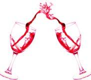 Dos vidrios de chapoteo del extracto del vino rojo aislado en blanco Fotografía de archivo libre de regalías