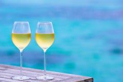 Dos vidrios de fondo sabroso del vino blanco el mar Fotos de archivo libres de regalías