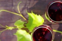 Dos vidrios de hojas del vino rojo y de la uva en una superficie de madera Foto de archivo