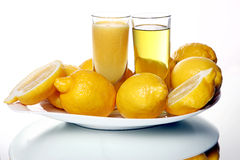 Dos vidrios de jugo de limón y los smoothies acercan a los limones frescos Foto de archivo